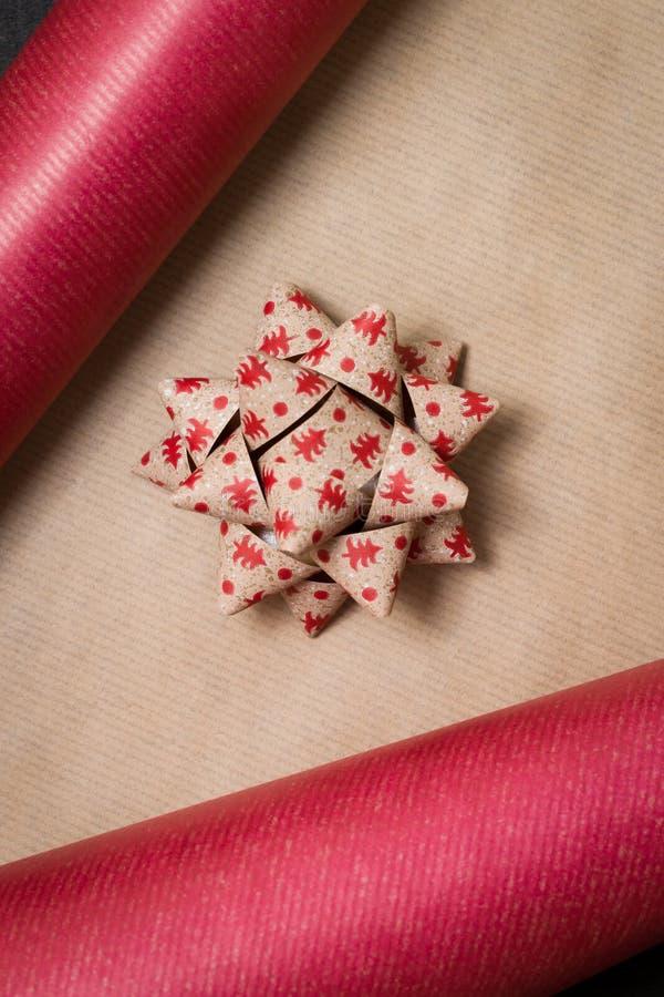 圣诞礼物的Preperation -包装纸和丝带弓flatlay在黑暗的木桌上 免版税库存图片