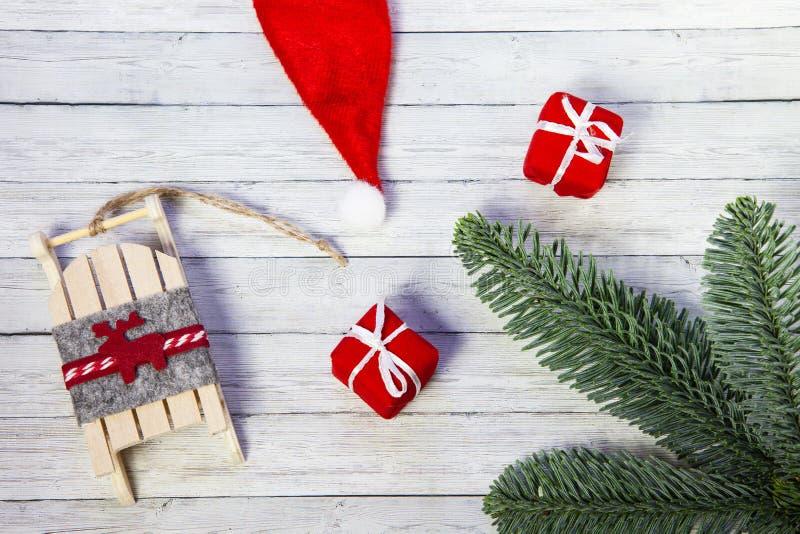 圣诞礼物箱子、圣诞老人的雪橇和冷杉分支在木背景,顶视图 免版税库存照片
