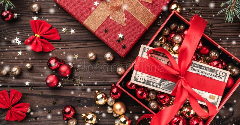 圣诞礼物,金钱包装与红色松驰,Xmas项目,在木背景 顶视图 作用雪花 库存图片