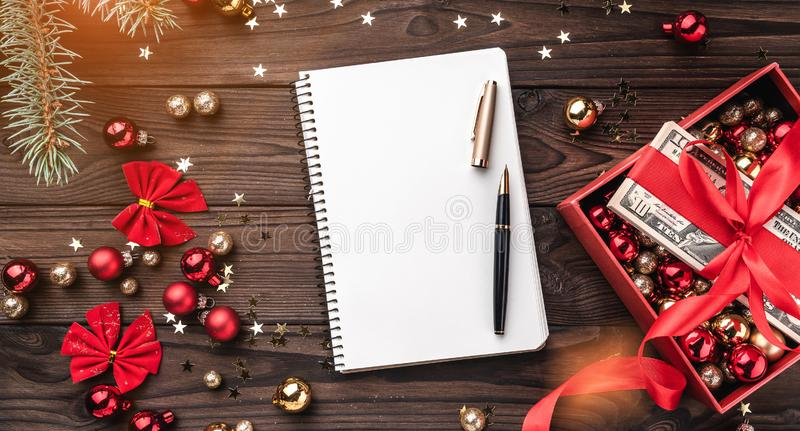 圣诞礼物,金钱包装与红色松驰,Xmas项目,在木背景 顶视图 在笔记本的文本空间 库存照片