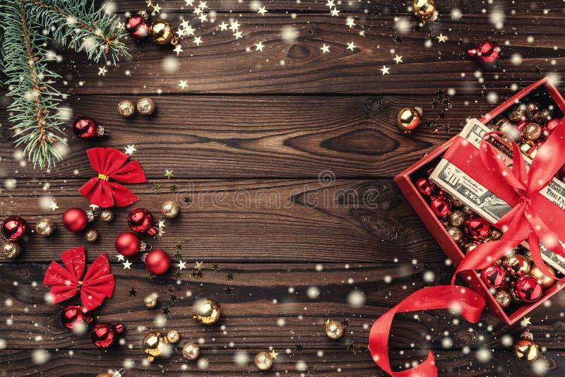 圣诞礼物,金钱包装与红色松驰,Xmas项目,在木背景 顶视图 文本的空间 作用雪花 免版税库存图片