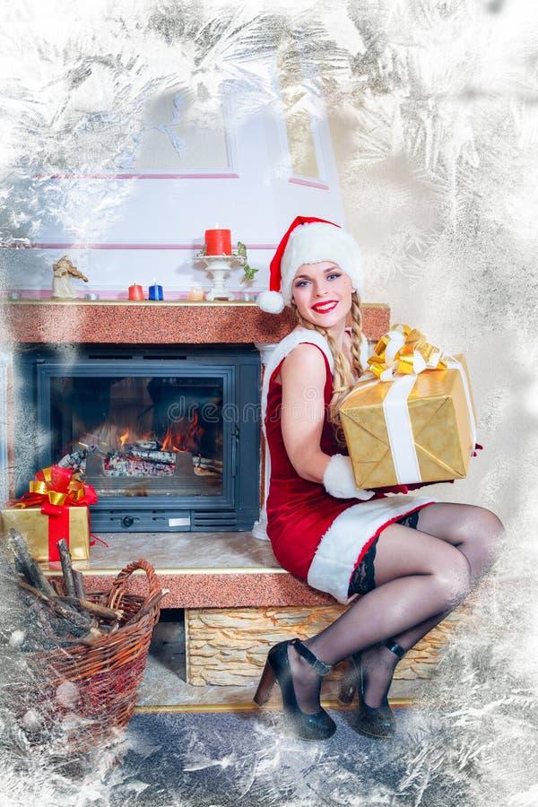 圣诞老人一个红色礼服和帽子的美丽的妇女  图库摄影