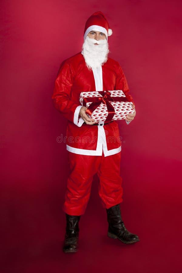 圣诞老人交付一件美丽的礼物 免版税库存图片