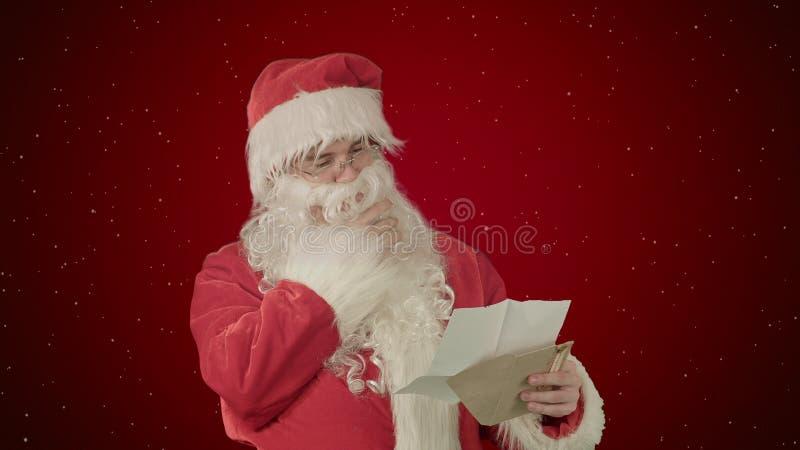 圣诞老人从孩子的读书信件与雪的红色背景的 免版税库存图片