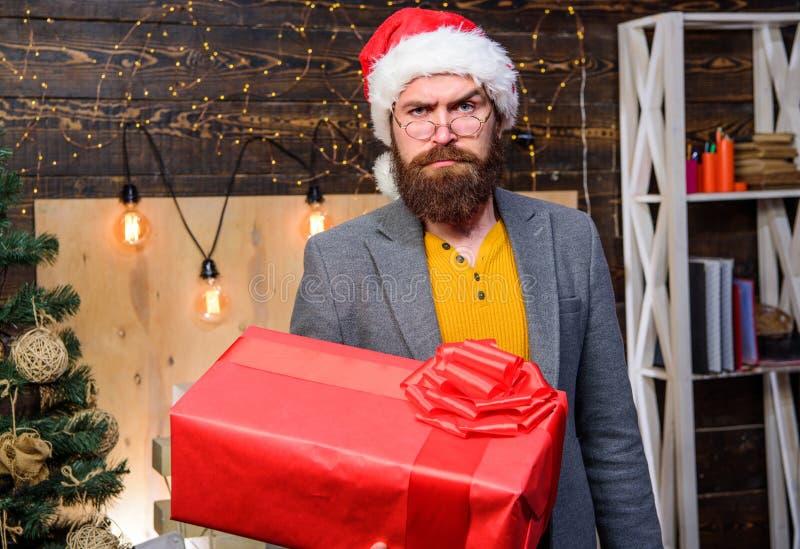 圣诞老人传讯者 人圣诞老人帽子交付礼物 被传播的幸福和喜悦 有镜片的有胡子的人运载当前箱子 库存图片