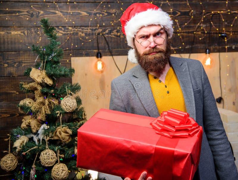 圣诞老人传讯者 礼物交付 人圣诞老人帽子交付礼物 被传播的幸福和喜悦 有镜片的有胡子的人运载 免版税图库摄影