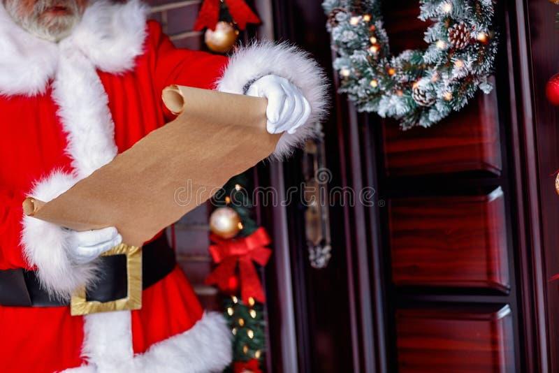 圣诞老人名单拿着纸卷纸的圣诞老人 免版税库存图片