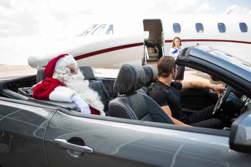 圣诞老人和汽车夫敞篷车的,当时 库存照片