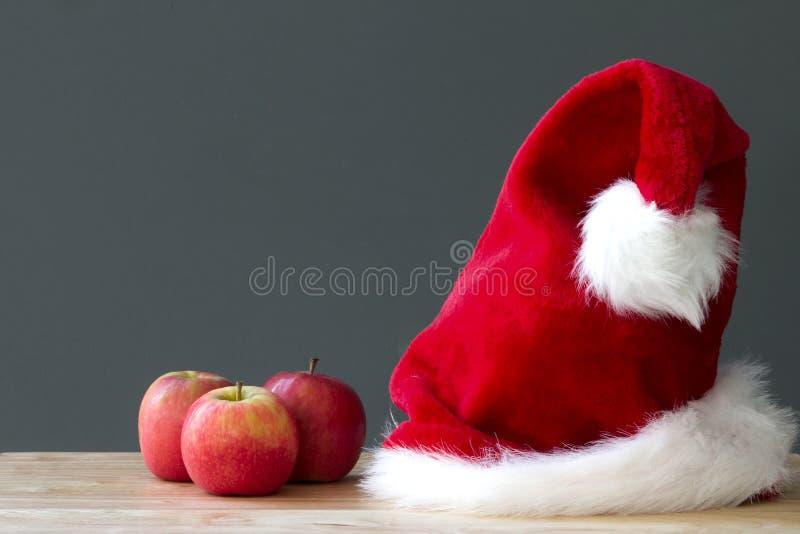 圣诞老人圣诞节红色帽子和三个苹果在桌上结果实 免版税库存图片