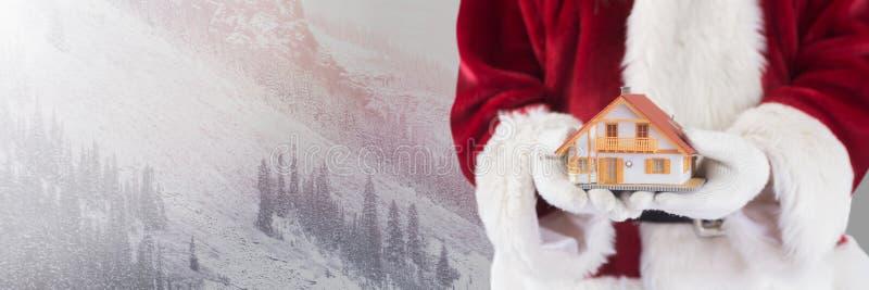 圣诞老人在与家的冬天在手上 图库摄影