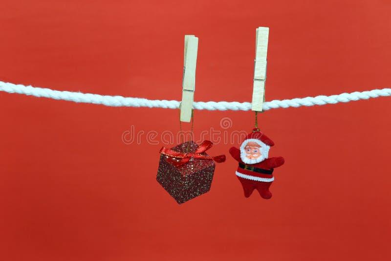 圣诞老人在晒衣绳的玩偶吊和有拷贝空间有红色背景 免版税库存照片