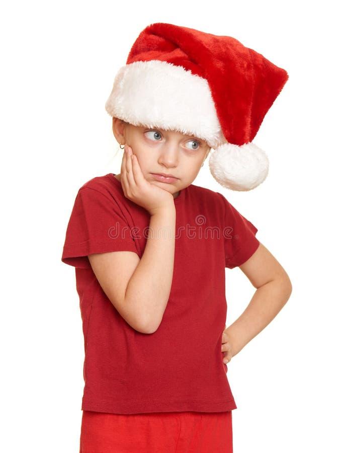 圣诞老人在白色被隔绝的帽子画象的,圣诞节假日概念哀伤的女孩孩子 免版税库存照片