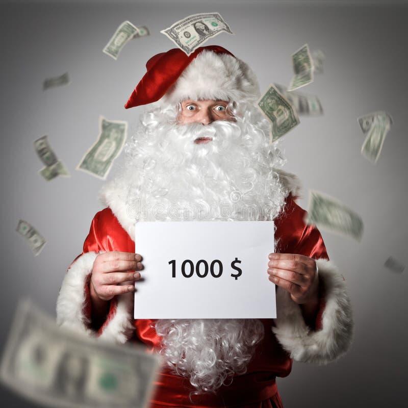 圣诞老人在他的手上拿着白皮书 一千 免版税库存图片