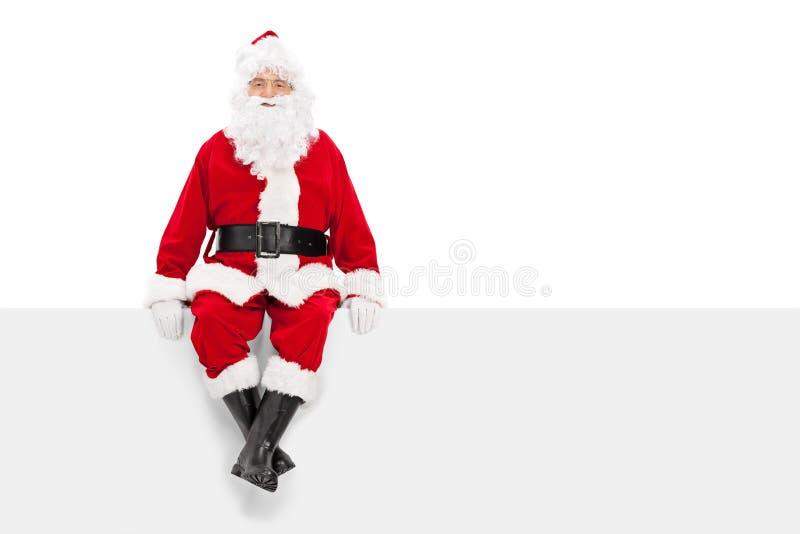 圣诞老人坐一个空白的广告牌 免版税库存图片