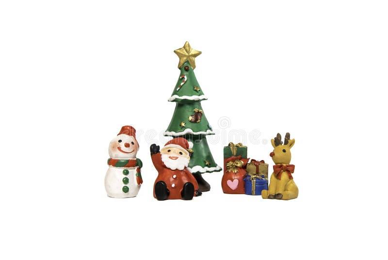 圣诞老人坐在圣诞树和礼物附近的雪人和驯鹿 免版税图库摄影