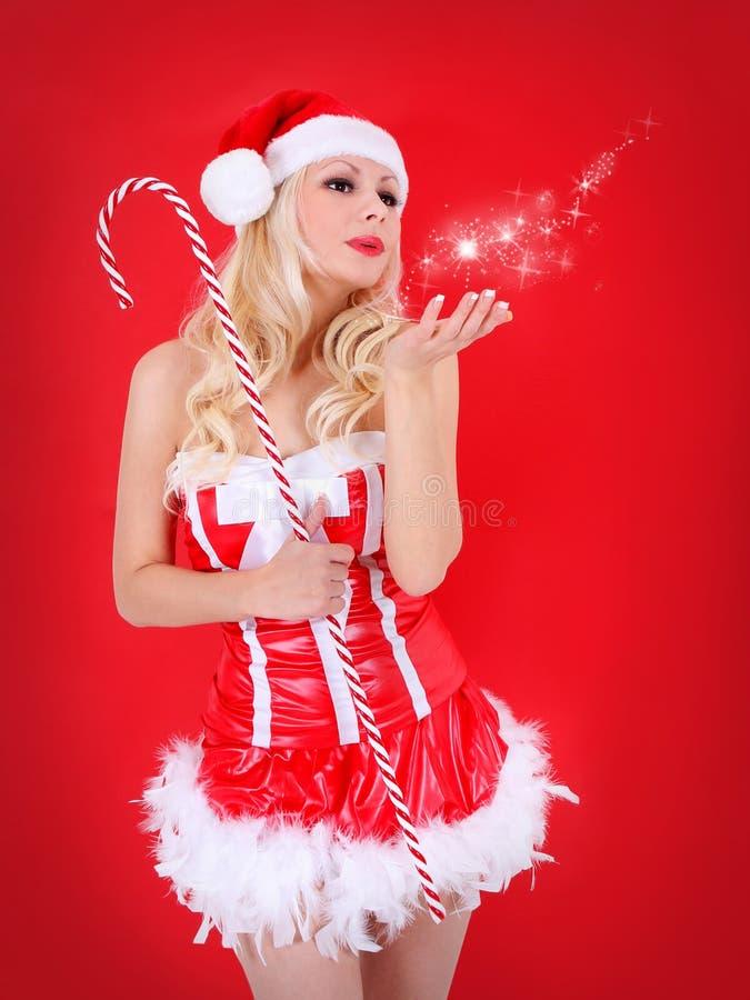 圣诞老人女孩。有圣诞节帽子吹的星亲吻的白肤金发的妇女 免版税库存图片