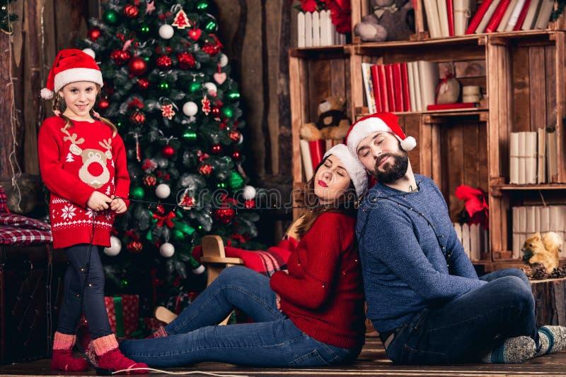 圣诞老人女孩包裹了她的有诗歌选的父母在圣诞装饰背景  免版税图库摄影