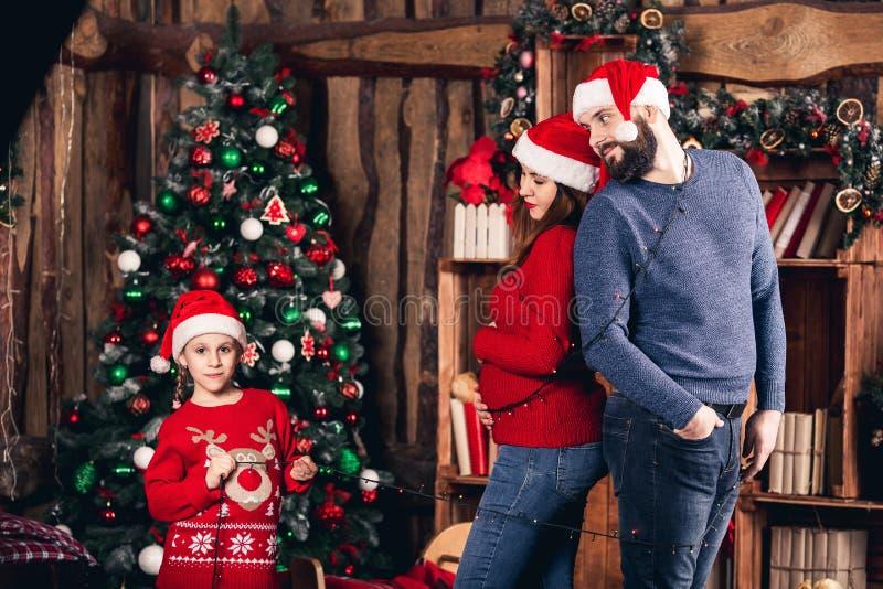 圣诞老人女孩快乐地包裹她的有诗歌选的父母 图库摄影