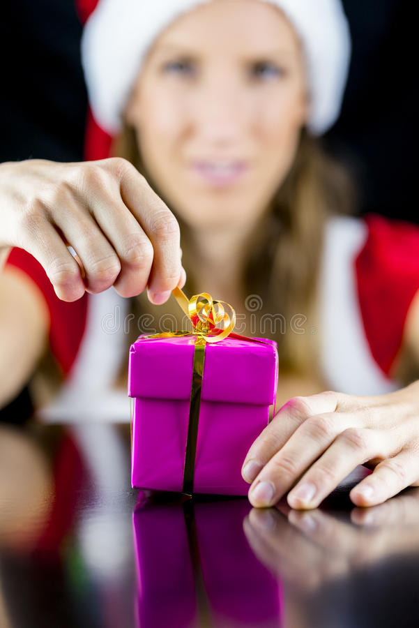 圣诞老人小姐打开桃红色的包裹了礼物盒 免版税库存图片