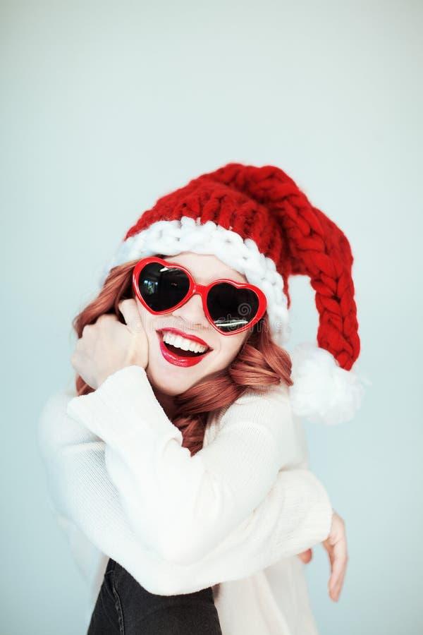 圣诞老人小的帮手 有圣诞老人帽子的美丽的愉快的少妇,完善组成,红色唇膏和心脏形状太阳镜 免版税库存照片