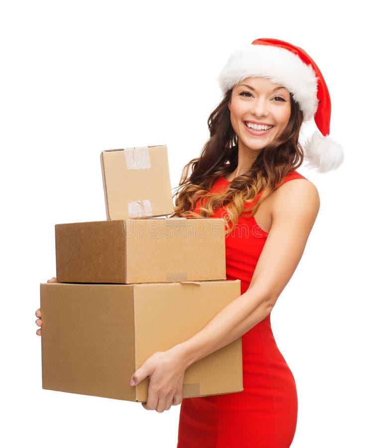 圣诞老人帮手帽子的微笑的妇女有小包的 免版税图库摄影