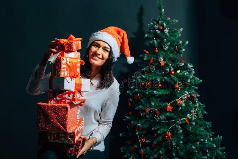 圣诞老人帮手帽子的微笑的妇女有许多礼物盒的 免版税库存照片