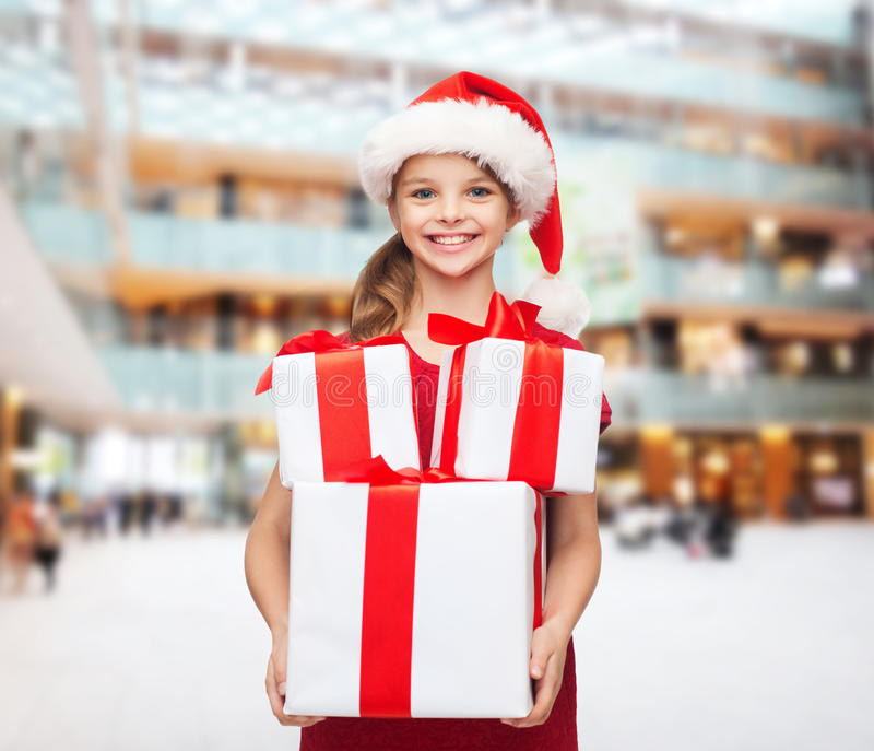 圣诞老人帮手帽子的微笑的小女孩有礼物的 库存照片