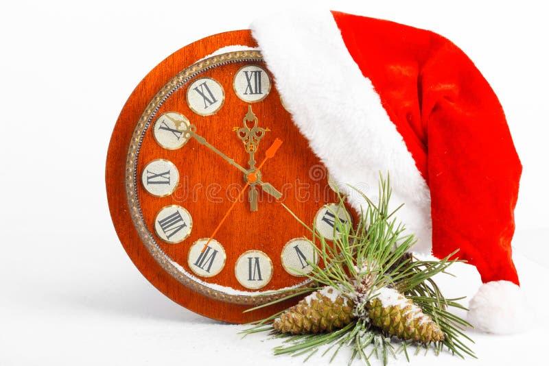 圣诞老人帽子、时钟和在背景隔绝的圣诞树 库存照片