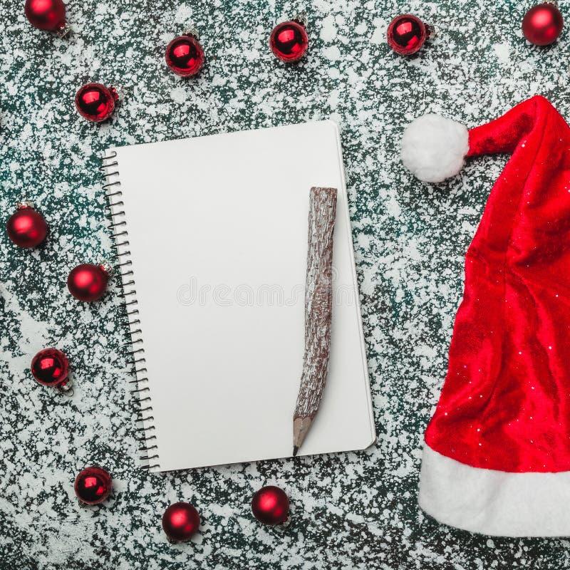圣诞老人帽子、xmas球和空白的笔记薄在土气雪背景 寒假题材 免版税库存照片