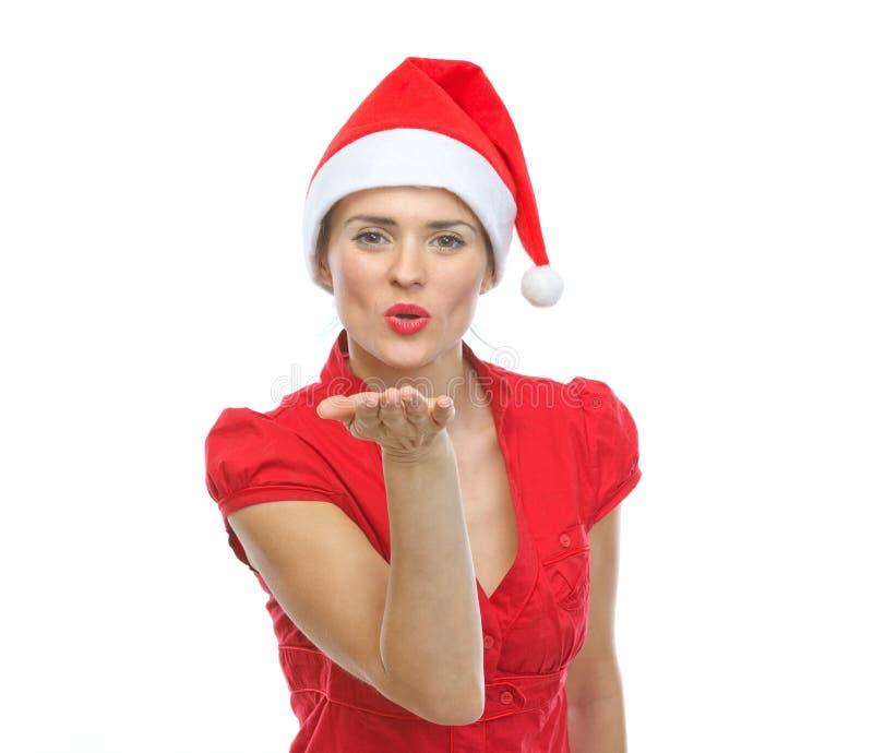 圣诞老人帽子吹的航空亲吻的微笑的少妇 免版税库存图片
