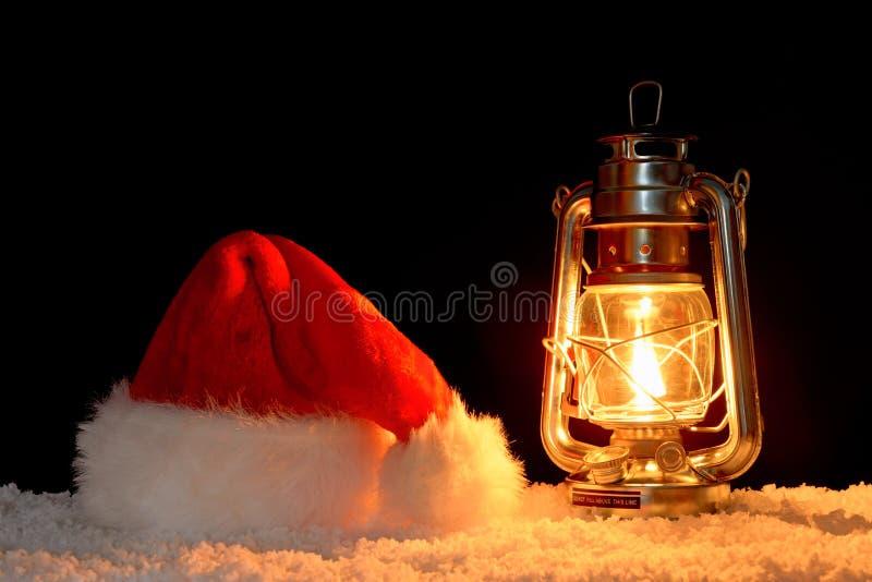 圣诞老人帽子和灯笼在雪 免版税库存图片