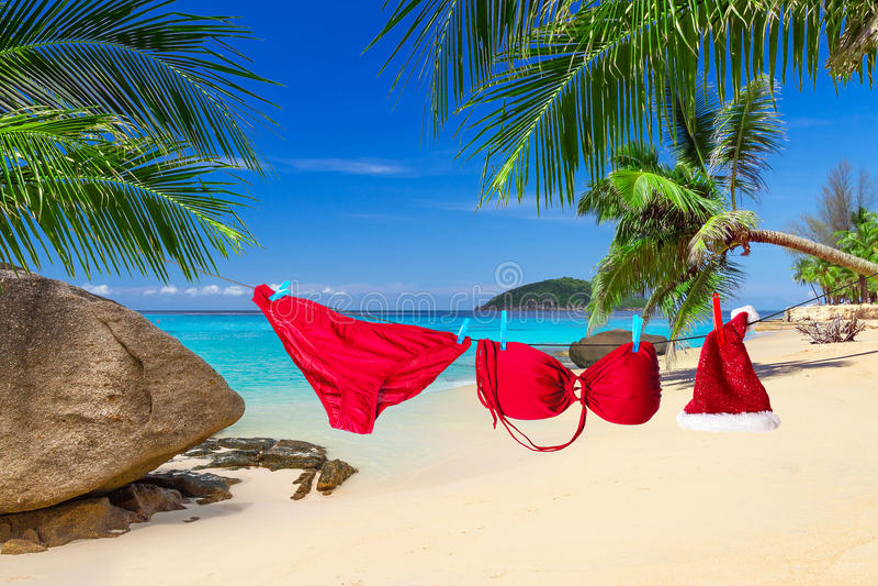圣诞老人帽子和红色比基尼泳装在热带海滩 库存照片