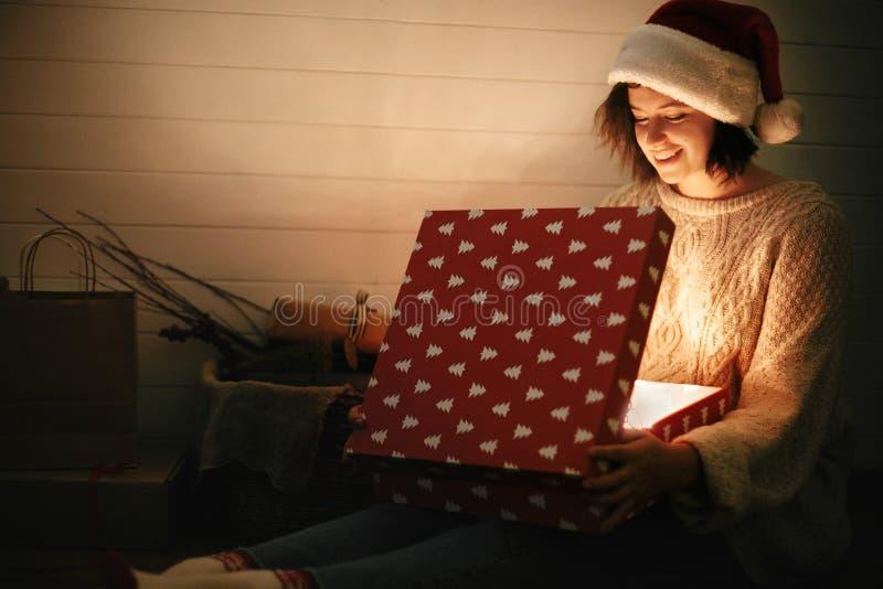 圣诞老人帽子和舒适毛线衣开头圣诞礼物箱子的时髦的愉快的女孩有在礼物背景的不可思议的光的在黑暗的 图库摄影