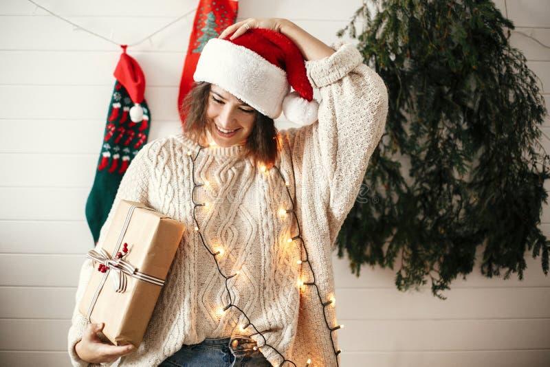 圣诞老人帽子和舒适毛线衣藏品圣诞礼物箱子的时髦的愉快的女孩在现代圣诞树,光背景和 库存照片