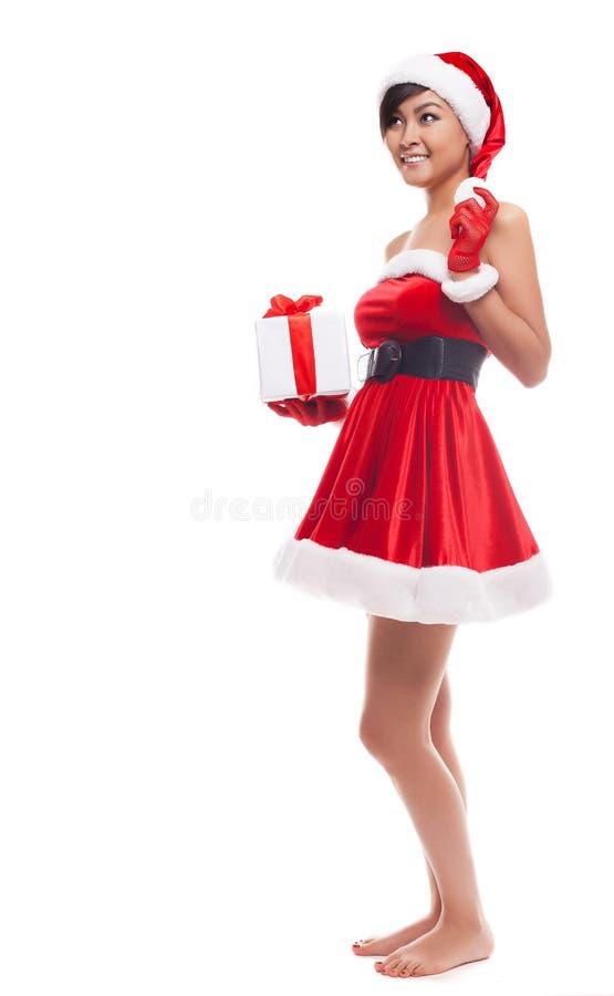 圣诞老人帽子圣诞节妇女立场和拿着圣诞节礼物smi 免版税库存图片