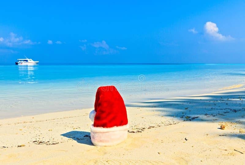 圣诞老人帽子在海滩 免版税库存图片