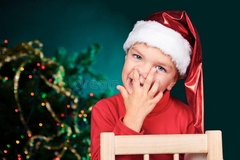 圣诞老人帽子挑选鼻子的小的男孩 图库摄影