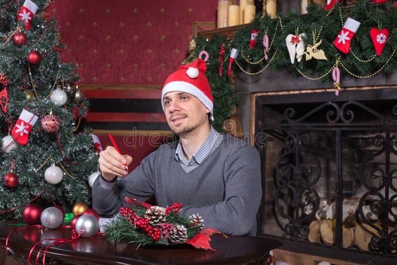 圣诞老人帽子文字圣诞节信件的年轻人 免版税库存照片
