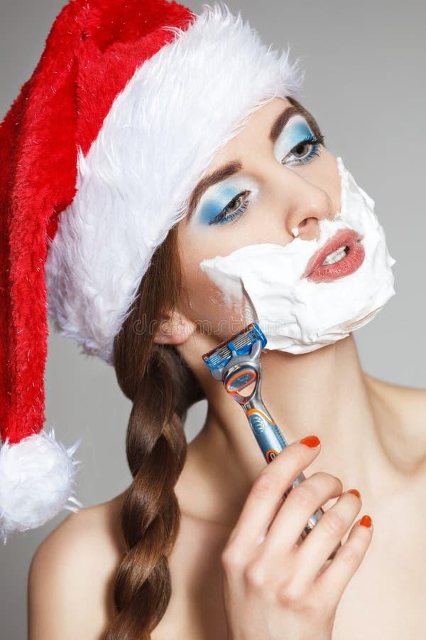 圣诞老人帽子的一名美丽的妇女刮她的在刮的泡沫的面孔与人` s剃刀 库存图片