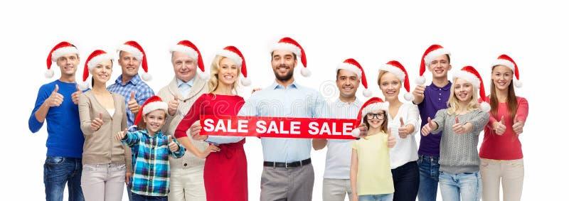 圣诞老人帽子的人们有销售的签字在圣诞节 免版税库存图片