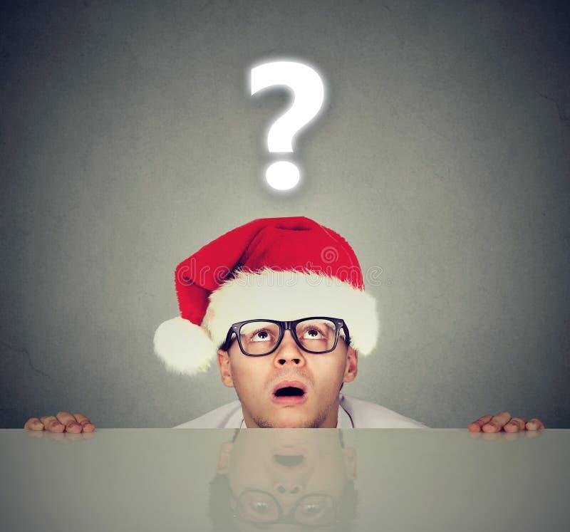 圣诞老人帽子的人有问号的对礼物感到奇怪 库存照片