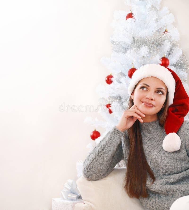 圣诞老人帽子的体贴的少妇在圣诞树旁边 免版税图库摄影