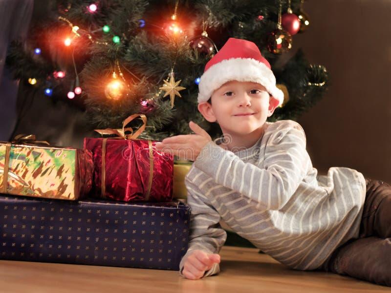 戴圣诞老人帽子的可爱的男孩在圣诞树附近 图库摄影