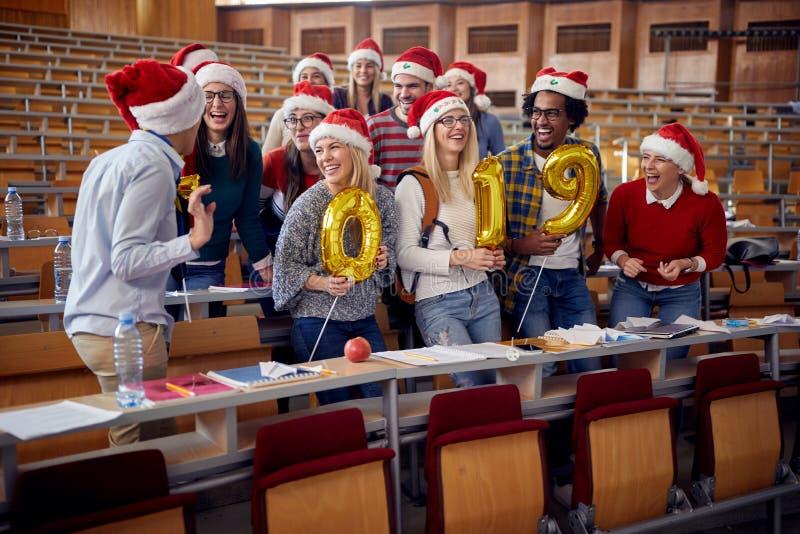 圣诞老人帽子的同事 获得乐趣在大学的新年庆祝 免版税库存照片