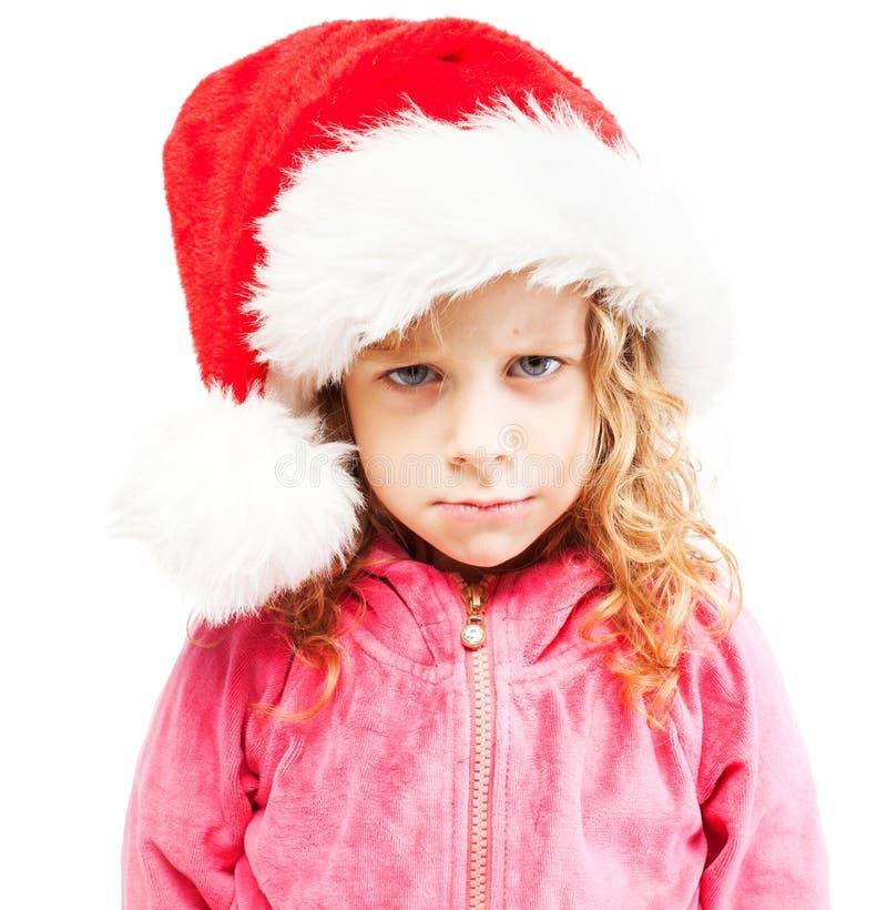 圣诞老人帽子的哀伤的女孩 免版税库存图片