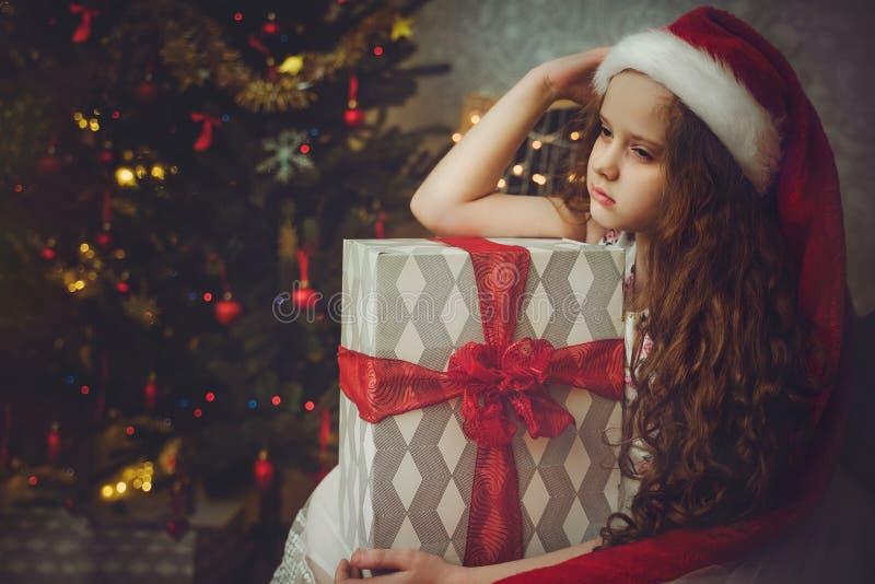 圣诞老人帽子的哀伤的小女孩 免版税库存照片