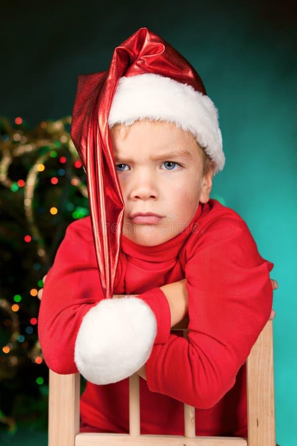 圣诞老人帽子的哀伤的小的男孩 库存照片