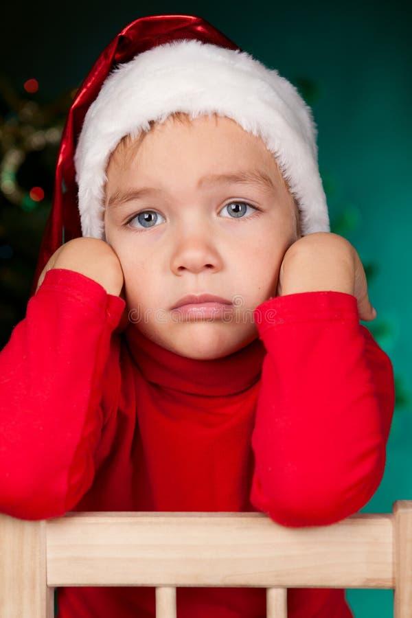 圣诞老人帽子的哀伤的小的男孩 库存图片