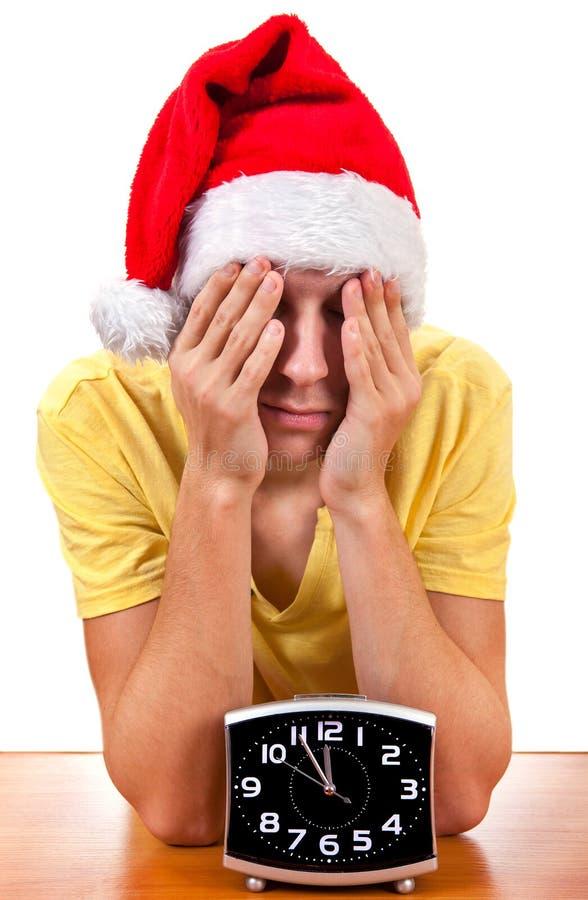 圣诞老人帽子的哀伤的年轻人 库存照片