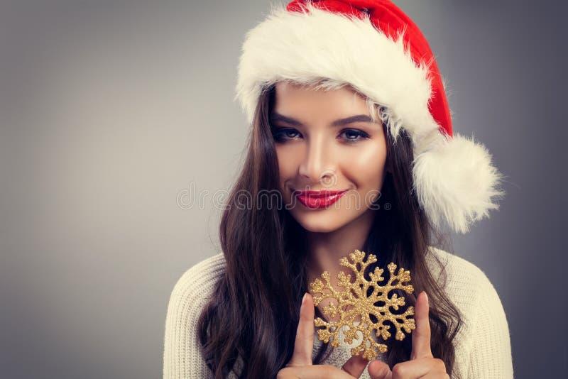 圣诞老人帽子的圣诞节妇女微笑和拿着冬天雪花的 免版税库存照片